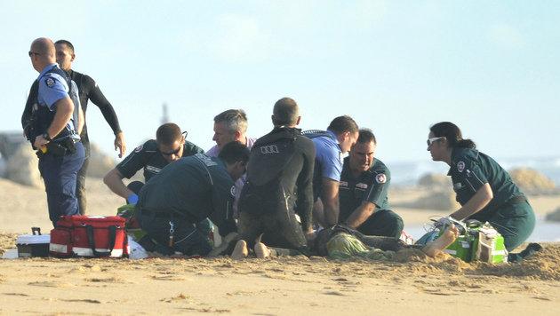 Ersthelfer kümmern sich um den schwerverletzten Surfer. (Bild: APA/AFP/Mandurah Mail/Marta Pascual Juanola)