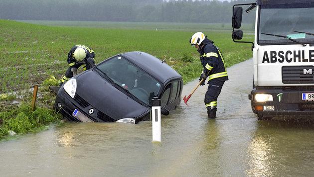 Einsatzkräfte befreien einen Pkw aus einem überfluteten Straßengraben im Bezirk Braunau in OÖ. (Bild: APA/MANFRED FESL)