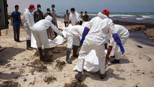 Helfer bergen Leichen an der libyschen Küste. (Bild: AFP)