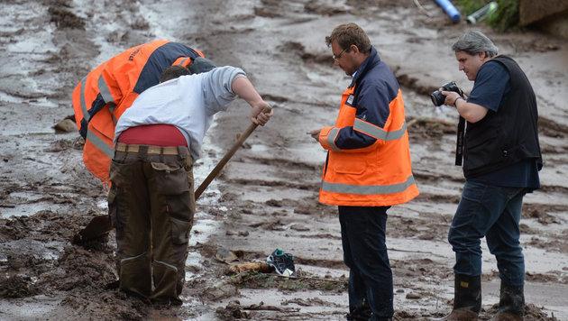 D: Aufräumarbeiten mit Flüchtlingen nachgestellt (Bild: APA/EPA/JAN-PHILIPP STROBEL)