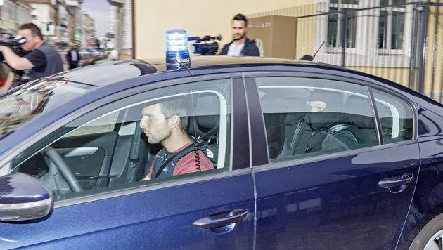 Einer der Verdächtigen wird zum Haftrichter gebracht. (Bild: APA/dpa/Ronald Wittek)