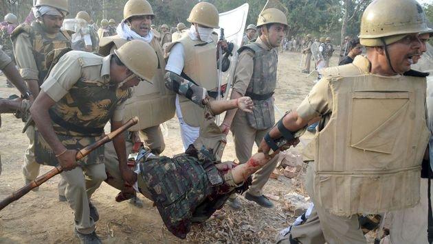 Ein verletzter Polizist wird von seinen Kameraden in Sicherheit gebracht. (Bild: APA/AFP/STR)