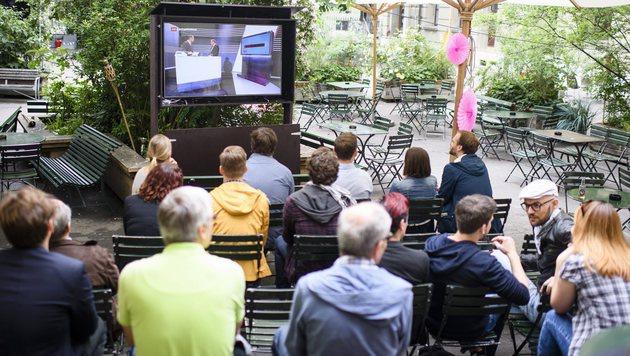 Gastgartenbesucher in Zürich verfolgen auf einem Bildschirm den Ausgang des Referendums. (Bild: EPA)