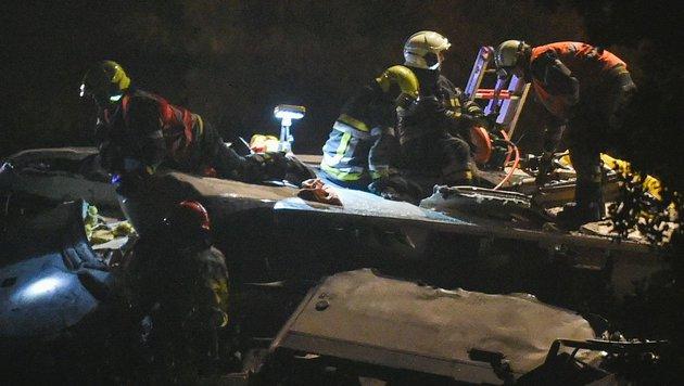 Rettungskräften befreien Passagiere aus einem zerstörten Waggon. (Bild: APA/AFP/John Thys)