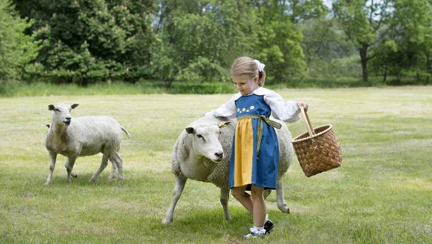 Prinzessin Estelle tollt mit den Schafen im Garten von Schloss Haga umher. (Bild: Kate Gabor/Kungahuset.se)