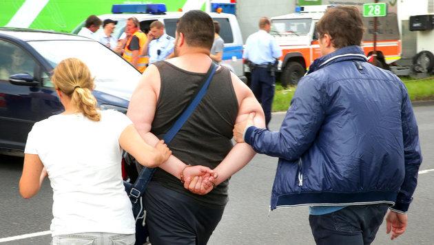 Einer der mutmaßlichen Brandstifter wird in Handschellen abgeführt. (Bild: APA/dpa/David Young)