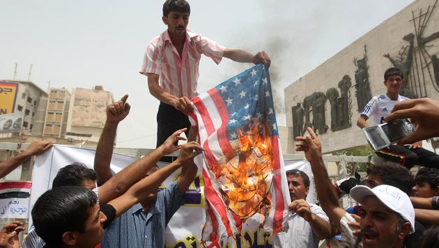 Männer im Irak verbrennen eine US-Flagge. (Bild: AHMAD AL-RUBAYE/AFP/picturedesk.com)