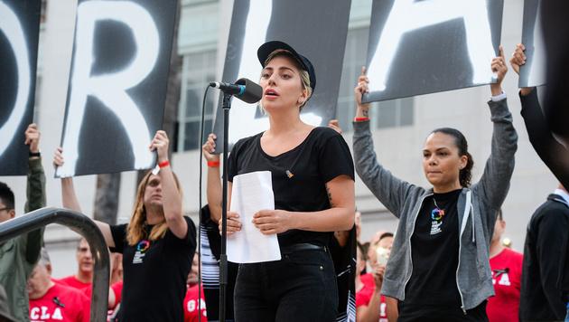 Sängerin Lady Gaga verlas in Los Angeles die Namen der Opfer. (Bild: AP)