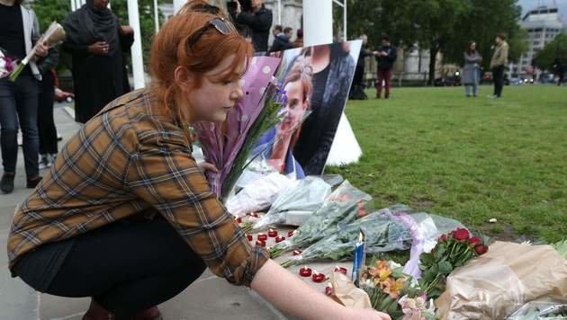 Trauernde stellen Kerzen und legen Blumen vor dem Parlament in London ab. (Bild: APA/AFP/DANIEL LEAL-OLIVAS)