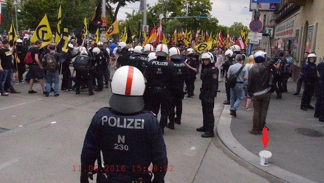 Dieses Polizeibild zeigt den Tatort kurz nach dem Steinwurf und den geworfenen Kübel (Pfeil). (Bild: LPD Wien)