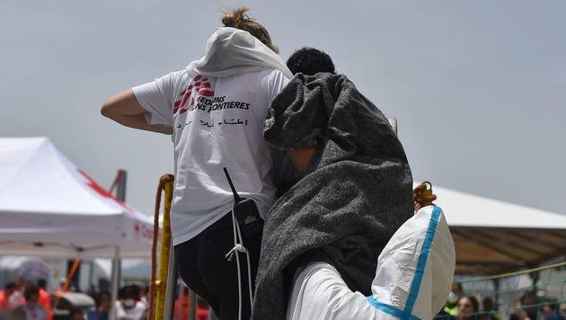 Eine Helferin von Ärzte ohne Grenzen bei der Begleitung eines Flüchtlings von Bord eines Schiffs (Bild: APA/AFP/GABRIEL BOUYS)