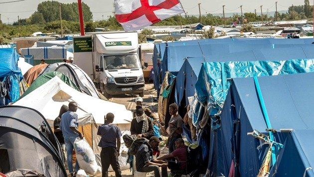 Die englische Flagge weht über dem provisorischen Flüchtlingslager in Calais. (Bild: APA/AFP/PHILIPPE HUGUEN)