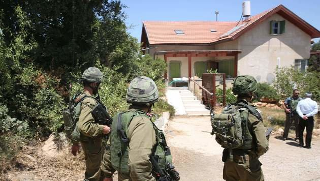 Das Haus, in dem der Mord passiert war, wurde später von israelischen Soldaten umringt. (Bild: APA/AFP/MENAHEM KAHANA)