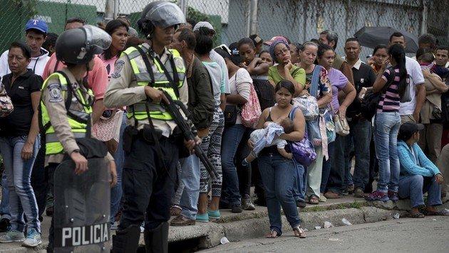Venezolaner warten vor einem bewachten Lebensmittelgeschäft in Caracas auf Einlass. (Bild: ASSOCIATED PRESS)