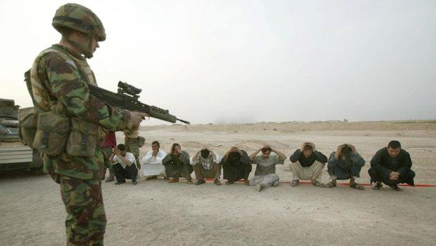 Britischer Soldat mit irakischen Gefangenen während des Kriegs im Jahr 2003 (Bild: APA/AFP/POOL/DAN CHUNG)