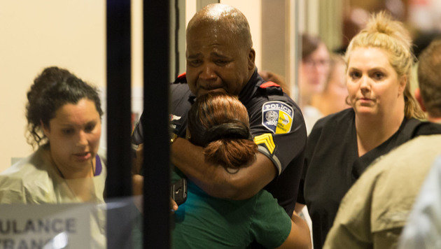 Ein Polizeioffizier trauert um seine kaltblütig erschossenen Kollegen. (Bild: ASSOCIATED PRESS)