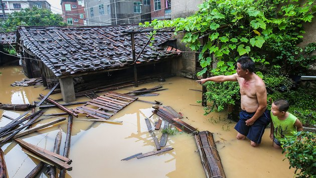 Bewohner vor ihren überfluteten Häusern in der Stadt Putian (Bild: APA/AFP/STR)