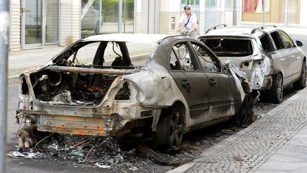 Die Demonstranten steckten auch Autos in Brand. (Bild: AP)