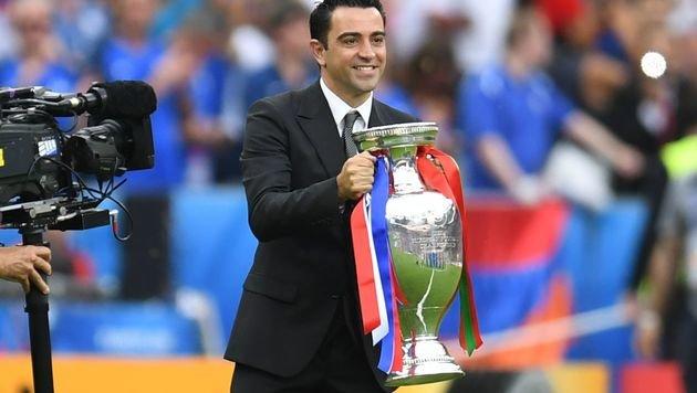 Der frühere spanische Nationalspieler Xavi präsentiert den EM-Pokal. (Bild: APA/AFP/PATRIK STOLLARZ)
