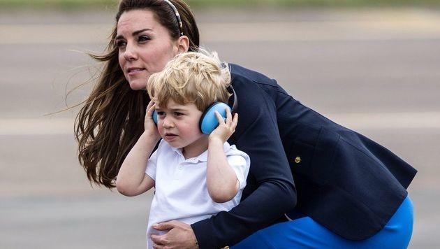 Der Mini-Royal bekam Kopfhörer gegen den Lärm. (Bild: AFP)