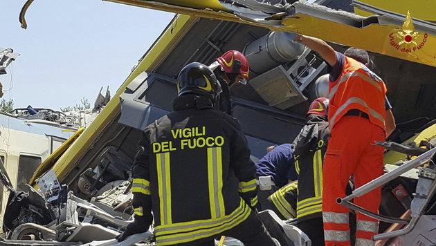 Feuerwehrleute untersuchen des Wrack eines der beiden Z�ge. (Bild: Associated Press)