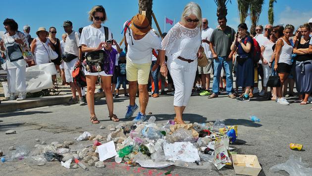 Einige Franzosen bespucken bei der Trauerfeier das symbolische Grab des Nizza-Attentäters. (Bild: Reinhard Holl)