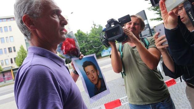 Naim Zabergja mit einem Foto seines getöteten Sohnes (Bild: APA/AFP/dpa/Karl-Josef Hildenbrand)