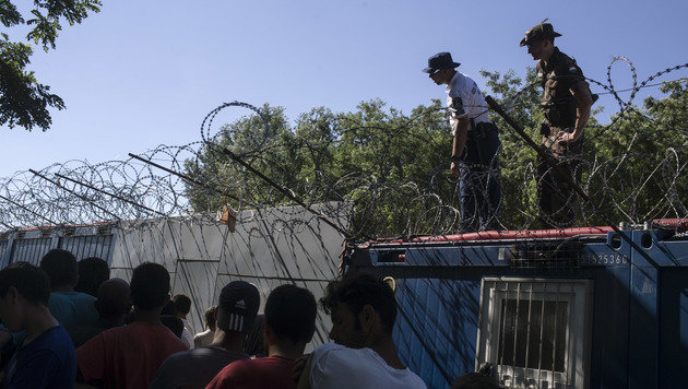 Ungarische Soldaten �berwachen die Lebensmittelausgabe an wartende Fl�chtlinge auf serbischer Seite. (Bild: ASSOCIATED PRESS)