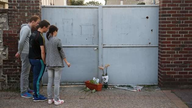 Menschen legen Blumen vor dem Haus von Pater Jacques Hamel nieder. (Bild: APA/AFP/MATTHIEU ALEXANDRE)
