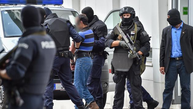 Einer der mutmaßlichen Dschihadisten wird aus dem Gerichtsgebäude gebracht. (Bild: APA/HARALD DOSTAL)