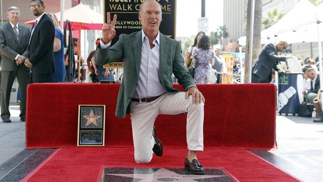 Michael Keaton kniet auf seiner Sternenplakette am Walk of Fame (Bild: AP)