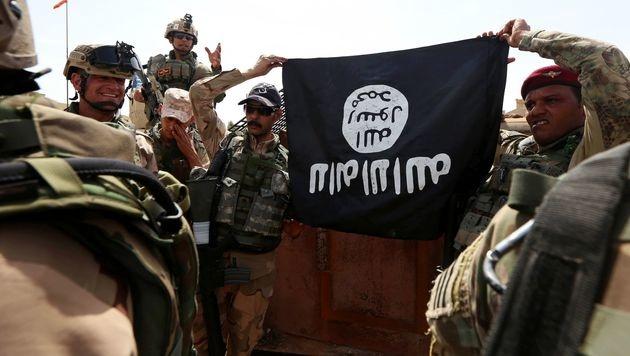 Irakische Soldaten mit einer auf den Kopf gestellten IS-Flagge. (Bild: APA/AFP/SAFIN HAMED)