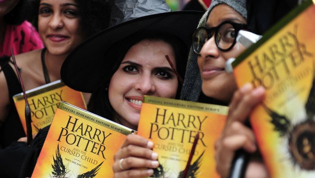 "Fans mit dem Buch ""Harry Potter and the Cursed Child"" (Bild: AFP or licensors)"