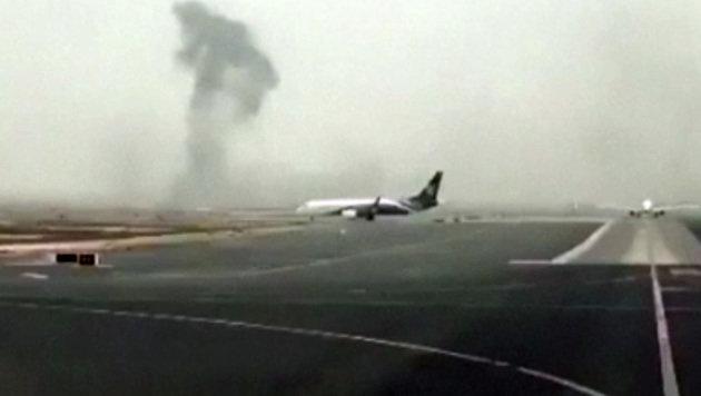 Eine Rauchwolke über einer Landebahn auf dem Dubai International Airport (Bild: Associated Press)