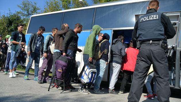 Ein deutscher Polizist mit Flüchtlingen am Grenzübergang in Freilassing (Bild: APA/BARBARA GINDL)