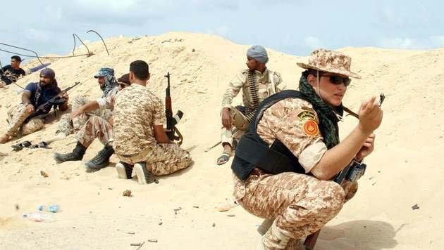 Libysche Truppen warten auf die n�chsten Luftangriffe auf Sirte. (Bild: APA/AFP/STRINGER)