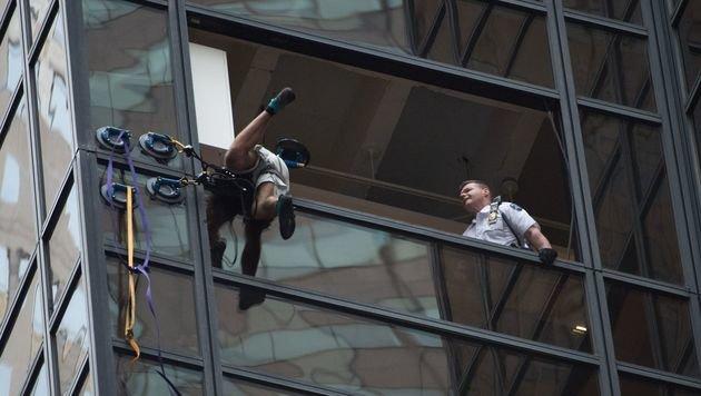 Im 21. Stockwerk war die Klettertour vorbei, Polizisten zerrten den jungen Mann ins Innere. (Bild: APA/AFP/BRYAN R. SMITH)