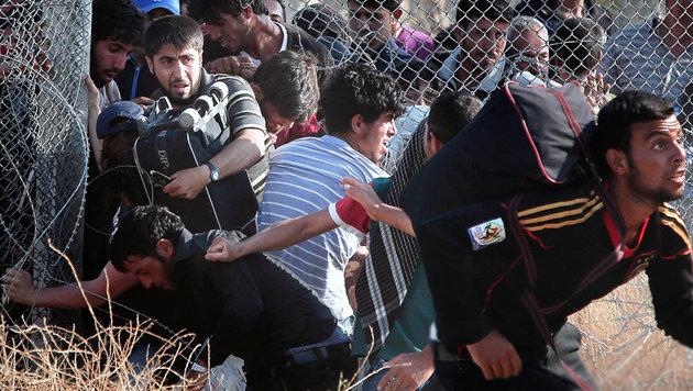 Flüchtlinge durchbrechen einen Grenzzaun zwischen Syrien und der Türkei. (Bild: AP)