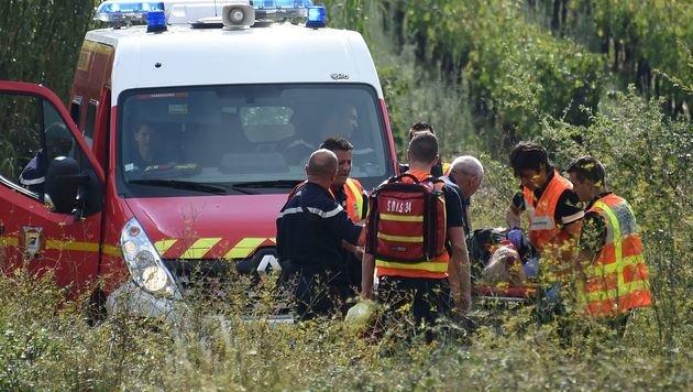 Rettungskräfte transportieren eine verletzte Person zum Rettungswagen. (Bild: APA/AFP/Sylvain Thomas)