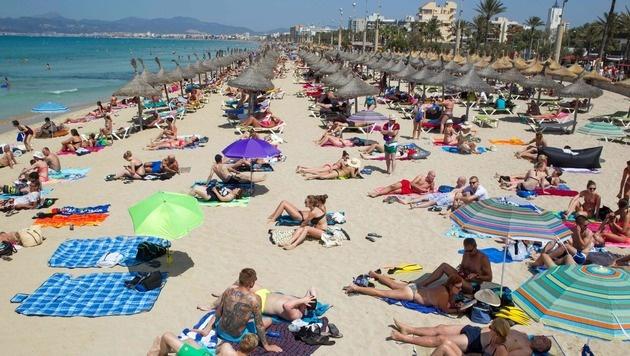 Touristen an einem Strand auf Mallorca (Bild: AFP or licensors)