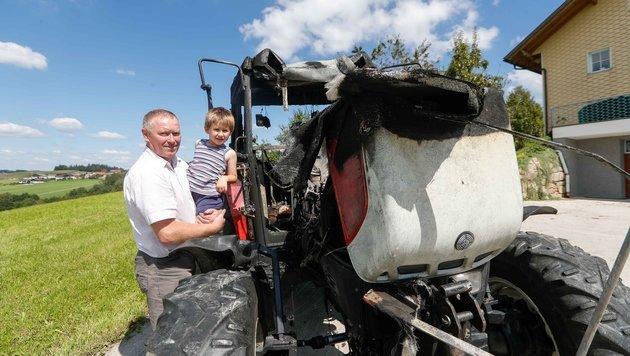 Der Held des Tages (4) mit Nachbar Josef Maurer neben dem völlig verbrannten Traktor. (Bild: Pressefoto Scharinger © Daniel Scharinger)