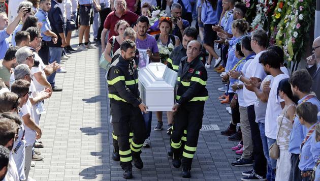 Feuerwehrmänner tragen den Sarg der kleinen Giulia. (Bild: Associated Press)