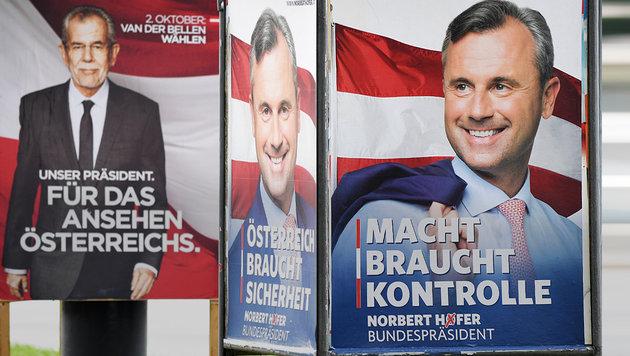 Van der Bellen und Hofer lächeln von Wahlplakaten. (Bild: APA/ROLAND SCHLAGER)