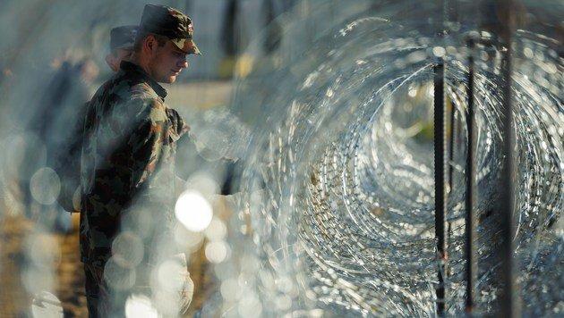 Slowenische Soldaten überprüfen einen Stacheldrahtzaun an der Grenze zu Kroatien. (Bild: APA/AFP/Jure Makovec)