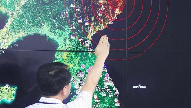 Ein südkoreanischer Experte zeigt das Epizentrum der Erdbebenwellen nach dem nordkoreanischen Test. (Bild: APA/AFP/YONHAP)