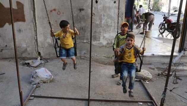 Spielende Kinder in einer von Rebellen gehaltenen Vorstadt von Damaskus (Bild: APA/AFP/AMER ALMOHIBANY)