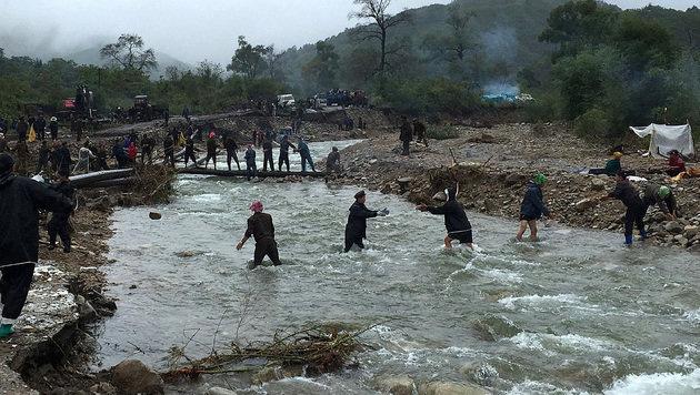 Freiwillige Helfer kämpfen gegen die Naturgewalten an. (Bild: APA/AFP/UNICEF DPRK/MURAT SAHIN)
