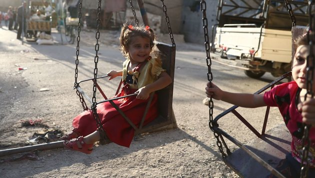 Spielende Mädchen in der von Rebellen kontrollierten Stadt Hamouria (Bild: APA/AFP/Abd Doumany)