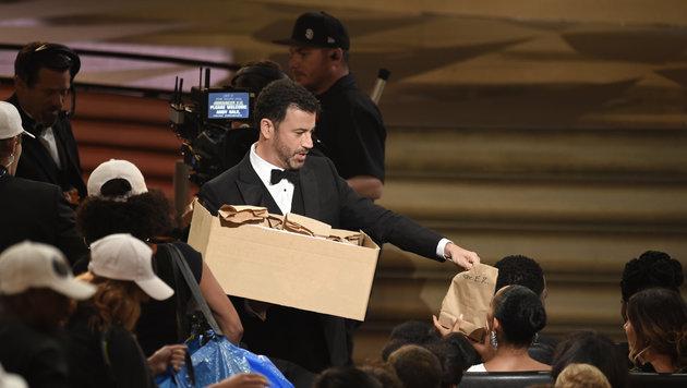 Emmy-Moderator Jimmy Kimmel verteilt als Gag Jausensackerln im Promi-Publikum. (Bild: Chris Pizzello/Invision/AP)