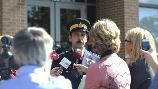Ein Polizeisprecher informiert die Medien über die Evakuierungen und Schulschließungen. (Bild: ASSOCIATED PRESS)